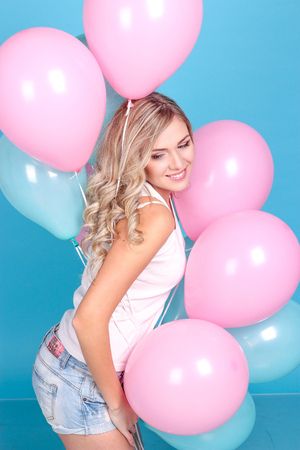 Young beautiful blonde girl holding balloons. Studio. Woman holding colorful balloons. Birthday.