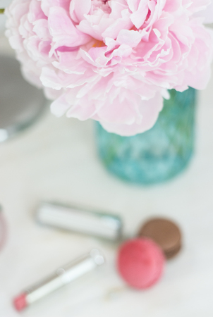 visage: Bouquet of pink peonies in a vase. Bouquet of peonies in a vase, macaroon, cosmetics on the table. Dressing table.