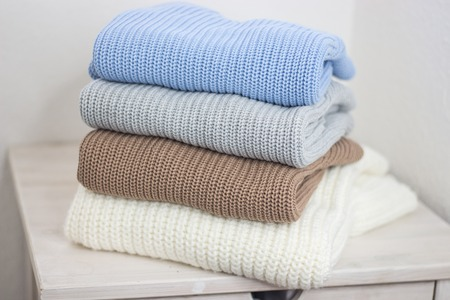 A pile of warm autumn clothing on a wooden shelf. Sweaters. Knitted winter wear. Cozy.