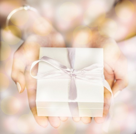 Young woman holding white gift box. Gift. Womens hands hold the white box.