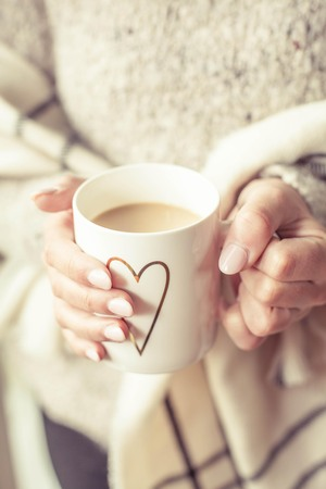 womens hands: Womens hands hold a hot mug of coffee. Young woman ukutannaja in plaid keeps a cup of cocoa. Holidays. Cozy autumn.