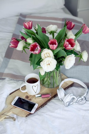 Romantic breakfast in bed. Bouquet of flowers. Roses and tulips. Spring. Valentine's Day. International Women's Day. Cozy. Summer. Stockfoto
