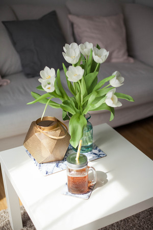 Interior. Room. A bouquet of tulips in a glass vase, a gold candlestick, a mug of lemonade on a white wooden table. Sofa, pillows. Spring. Its cozy.