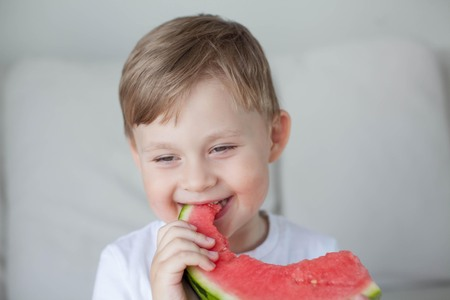 A small cute boy 4 years old is eating a watermelon. Summer. Heat. Watermelon. Portrait of a happy boy with a watermelon. Bright hues. Stock Photo