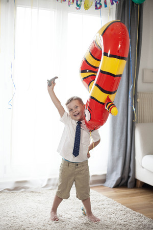 Portrait of a pretty boy 4 years old with balloons. Birthday. Happy child in a suit. Love.