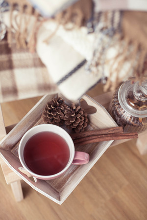 Plaids. A cup of hot tea. Autumn cozy interior. On a wooden chair is a stack of warm blankets. Candles, leaves, cones, basket, cinnamon. Book and glasses. Autumn. Winter.