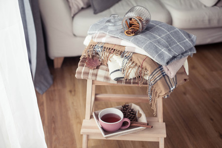 Plaids. A cup of hot tea. Autumn cozy interior. On a wooden chair is a stack of warm blankets. Candles, leaves, cones, basket, cinnamon. Book and glasses. Autumn.