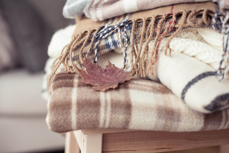 Blankets close up. Autumn cozy interior. A stack of warm blankets lie on a wooden chair. Autumn. Winter.