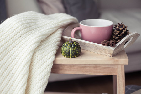 Knitted, warm sweaters, a cup of hot tea, autumn decor, a book, a pumpkin on a wooden chair. Cozy, autumn decor. Autumn interior, sofa. Autumn. Winter.