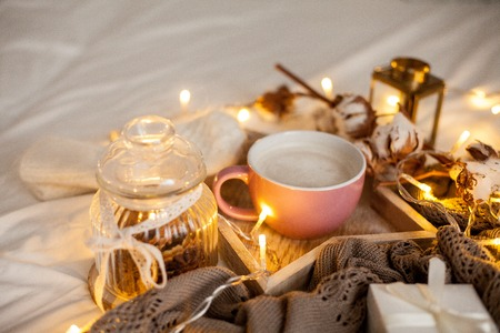 Mug of hot cappuccino on a wooden tray is on the bed. Cozy decor. Breakfast. Mug, plaid, cotton, candle. Gift box and knitted mittens. Christmas lights. Holidays. Christmas. Autumn. Winter.