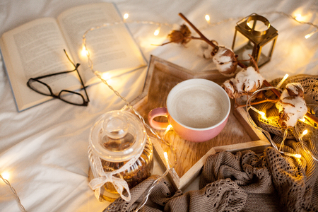 Mug of hot cappuccino on a wooden tray is on the bed. Cozy decor. Breakfast. Mug, plaid, cotton, candle. Book. Christmas lights. Holidays.