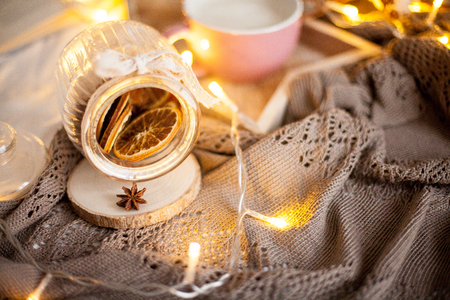 Jar of cinnamon, vanilla and citrus. Mug of hot cappuccino on a wooden tray is on the bed. Cozy decor. Book. Christmas lights. Holidays.