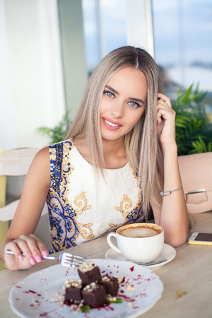 Young beautiful blonde with blue eyes is sitting in a cafe. A young woman holds a cappuccino mug in her hands. Portrait of a young happy woman. Fashion. Makeup. Summer.