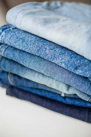 Jeans, denim cotton, blue. Stack of jeans in the interior. Clothing. Cozy.