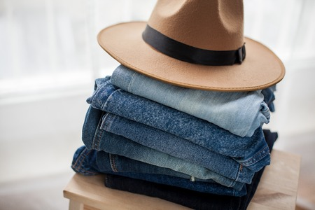 Jeans, felt hat, denim cotton, blue. Stack of jeans in the interior. Clothing.Cozy. Archivio Fotografico