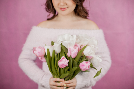 Close-up Young woman holding Bouquet of pink Tulips Pink background Spring