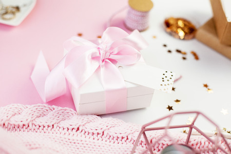 Spring decor. White gift box with a pink ribbon, sparkles, ribbons, a candle, jewelry, a notebook on a pink and white background. Mother's day.
