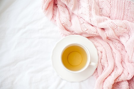 Beautiful white cup with tea on the bed, pink knitted plaid. Breakfast in bed. Morning. Spring.