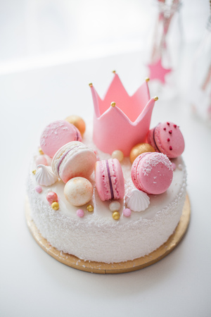 Beautiful cake for a girl with a decor. Crown of mastic, macaroons. Birthday.
