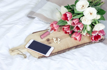 A wooden board, a plaid, a bouquet of tulips, decorations, a telephone, cosmetics lie on a white bed. Spring.