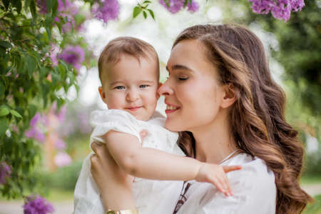 Beautiful young mother and little cute daughter are happy near the lilac. Portrait of mom and daughter. Zdjęcie Seryjne