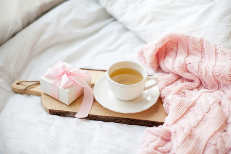 White mug with tea, gift box with ribbon on the bed. Breakfast in bed. Cozy. Pink plaid. Cotton. Spring.