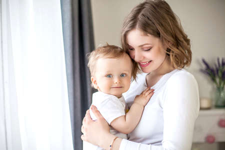 Beautiful mother and little son 9 months in the home interior. Baby. Motherhood.
