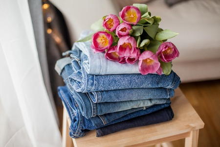 A bouquet of tulips lying on a pile of jeans. Clothing. Spring. Reklamní fotografie - 122615980