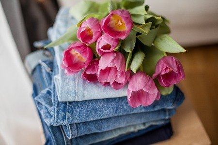A bouquet of tulips lying on a pile of jeans. Clothing. Spring. Reklamní fotografie - 122615982