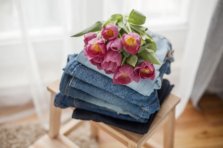 A bouquet of tulips lying on a pile of jeans. Clothing. Spring.