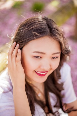 A young beautiful Asian woman in a white dress walks in a flowered park. Sakura. Blooming trees. Stock Photo