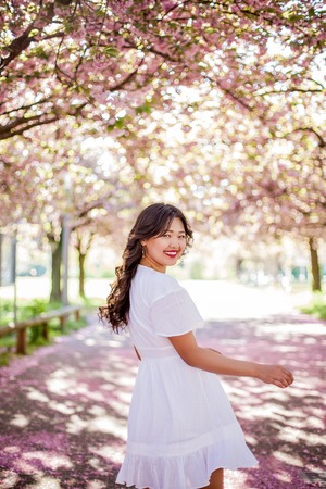 A young beautiful Asian woman in a white dress walks in a flowered park. Sakura. Blooming trees. Archivio Fotografico