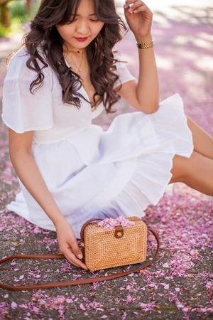 Close-up. A young beautiful woman in a white dress is holding a wicker bag. Sakura. Blooming trees.