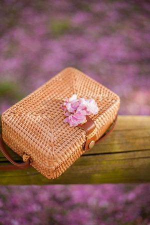 Wicker bag lies on a tree in a flowered garden. Sakura. Spring.