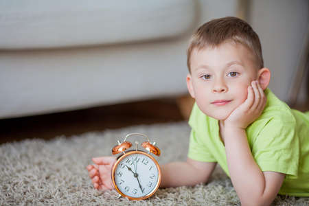 Cute little boy of 4 years old lies on the carpet and near the alarm clock. Morning. Awakening. Home.