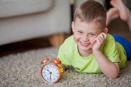 Cute little boy of 4 years old lies on the carpet and near the alarm clock. Morning. Awakening. Home. Foto de archivo
