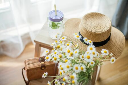 Little wicker women bag, a bouquet of daisies, lemonade with mint, wicker hat, wooden chair. Cozy.