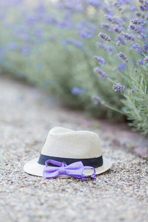 Wicker hat and bow tie lie near the blossoming lavender. Warm summer.