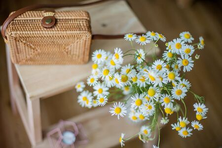 Small woven women bag, a bouquet of daisies. Cozy.