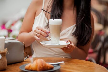 Close-up. Female hands hold a cup of cappuccino. French cafe. Bakery products. Summer. Stock fotó