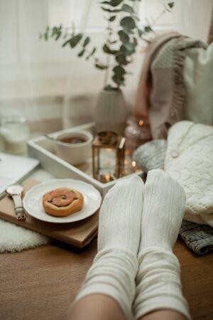 Toned photo. Autumn decor. Women's legs in knitted socks, a laptop, a mug of hot tea, a bun, candles. Cozy. Autumn. Fall mood.