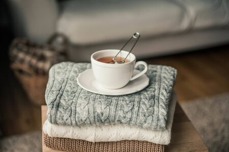 Toned photo. Autumn decor. A mug of hot tea, Knitted sweaters . Cozy. Autumn. Fall mood.