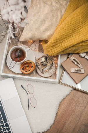 Toned photo. Autumn decor. A laptop, a mug of hot tea, a bun, candles. Cozy. Autumn. Fall mood.