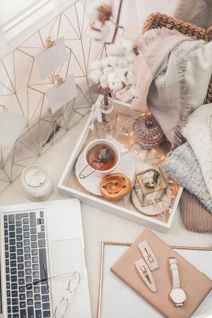 Toned photo. Autumn decor. A laptop, a mug of hot tea, a bun, candles. Cozy. Autumn. Fall mood.