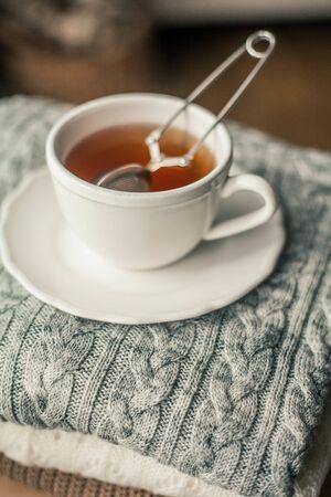 Toned photo. Autumn decor. A mug of hot tea, Knitted sweaters . Cozy. Autumn. Fall mood.