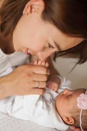 Close-up. The handle of the baby in mothers hands. Cute newborn baby sleeping in mothers arms. Stock Photo