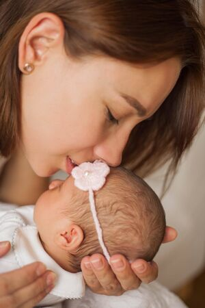 Close-up. Mom gently kisses the baby. Cute newborn baby sleeping in mothers arms. Motherhood. Stock Photo
