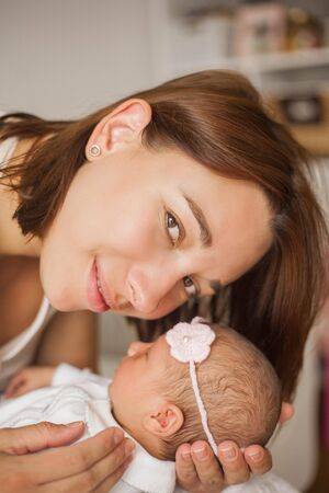 Close-up. Cute newborn baby sleeping in mothers arms. Motherhood.