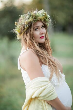 Portrait of a pregnant woman in the sun. Young beautiful pregnant woman with a wreath on her head in the field. Motherhood. Warm autumn. Banque d'images - 131956916