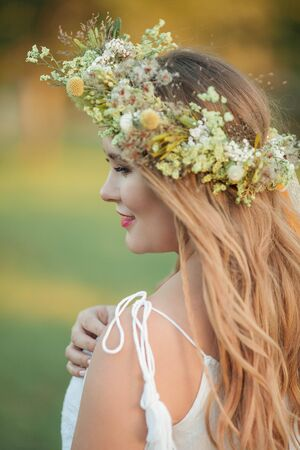 Close-up. Portrait of a pregnant woman in the sun. Young beautiful pregnant woman with a wreath on her head in the field. Motherhood. Warm autumn. Stock Photo